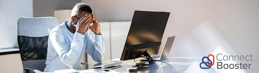 business man looking frustrated while sitting at his computer